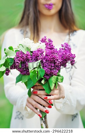 Woman holding delicate spring lilac flowers bouquet in her manicured hands and in the lips - stock photo