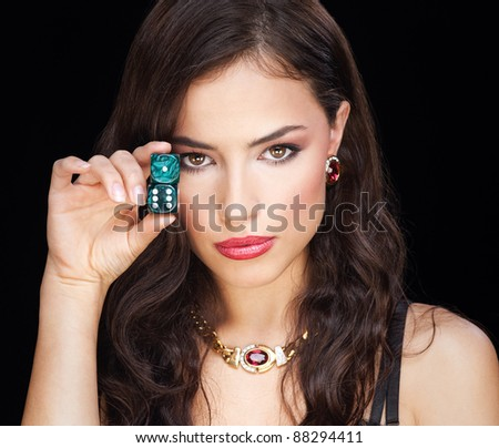 woman holding dices on black background - stock photo