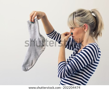 Woman holding dirty socks with her nose closed - stock photo