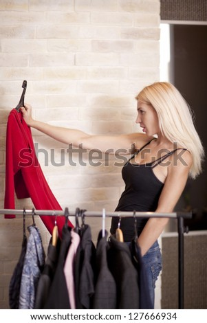 Woman holding dress on coathanger by clothing rail
