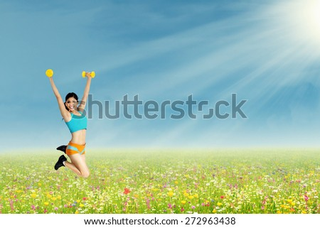 Woman holding dumbbells on her hands and jumping on the park