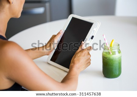 Woman holding electronic tablet while drinking a green detox juice, wearing sportive clothing. - stock photo