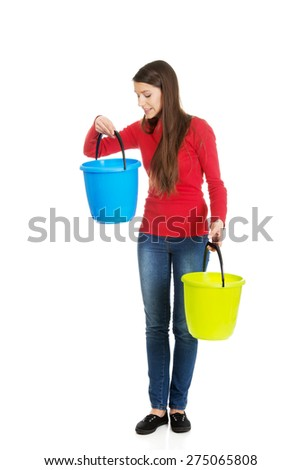 Woman holding empty colorful plastic buckets. - stock photo