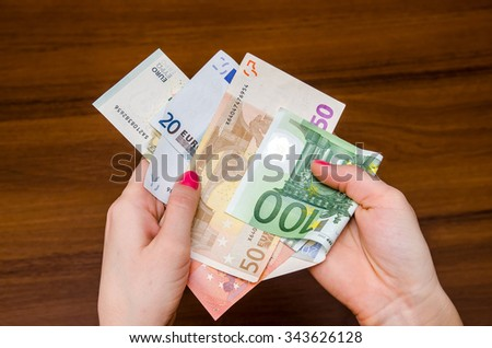 woman holding euro banknotes over wooden table