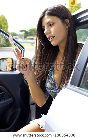 Woman holding europena euro money sitting in car - stock photo