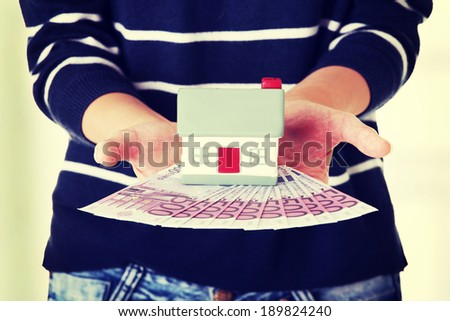 Woman holding euros bills and house model - real estate loan concept - stock photo