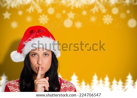 Woman holding finger to lips against blurred fir tree background