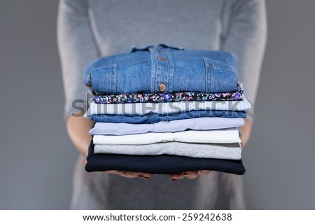 Woman holding folded clothes in hands - stock photo