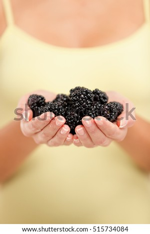 Woman holding fresh blackberries in hands closeup. Person showing handful of black berries fruits in woman hands. Blackberry fruit berry healthy diet concept.
