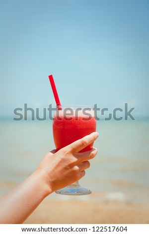 Woman holding fresh fruit cocktail on a tropical island beach