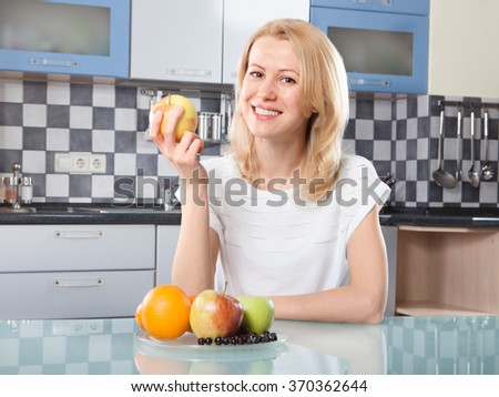 Woman holding  fresh fruits in hands at  the kitchen