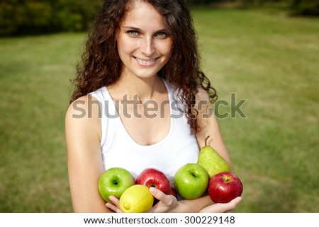 woman holding fruits. Outdoor - stock photo