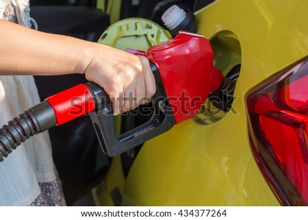 woman holding fuel nozzle red and refuel car yellow in gas station - stock photo