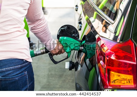 woman holding fuel pump in gas station.