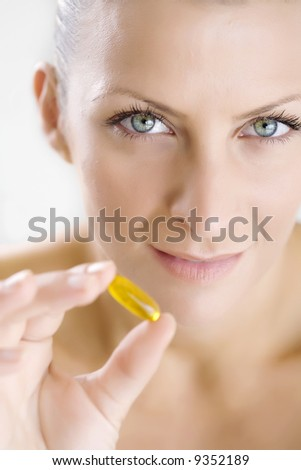 woman holding gelatin capsule, focus is on the eyes