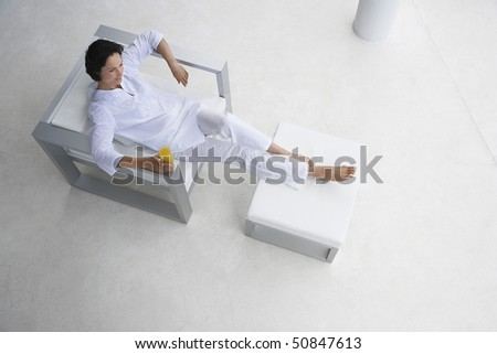 Woman holding glass of juice, reclining in armchair, elevated view