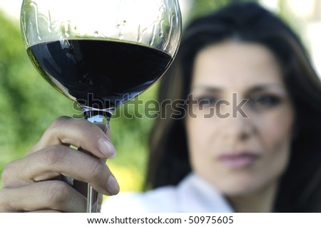 Woman holding glass of red wine - stock photo