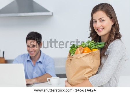 Woman holding groceries bag while her husband is on his laptop - stock photo