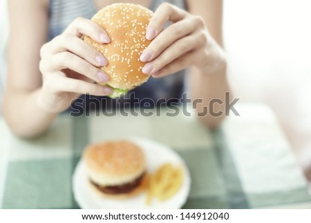 Woman holding hamburger and sitting at the table - stock photo