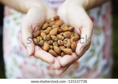 Woman Holding Handful Of Almonds - stock photo