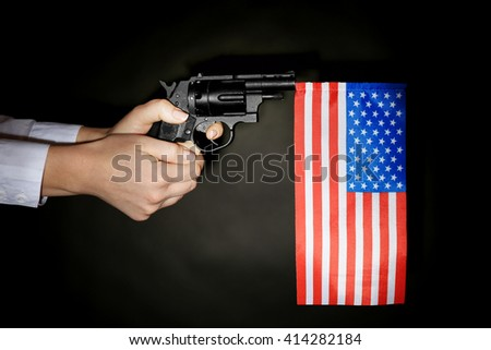 Woman holding handgun with inserted USA national flag on dark lighted background - stock photo