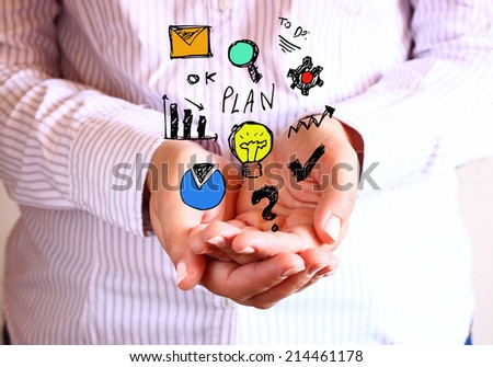 woman holding hands in cupped shape and drawings of charts and infographics. Close up image with selective focus. Business concept .  - stock photo