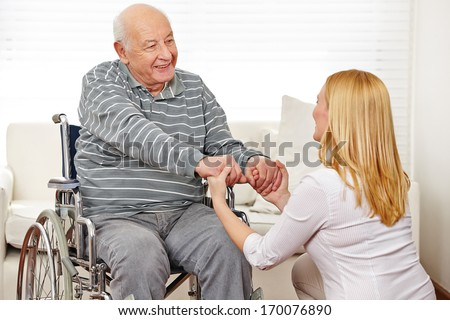 Woman holding hands of old man in wheelchair in a nursing home - stock photo