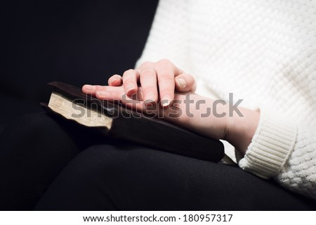 Woman holding hands over her holy bible and praying to God.