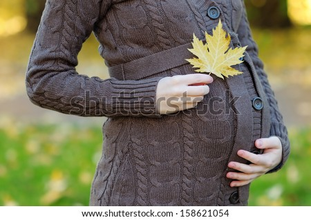 Woman holding hands with maple leaf on her pregnant belly, focus on hand - stock photo