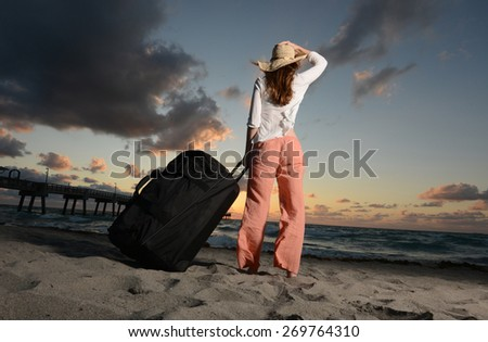 Woman holding hat on head while looking at the ocean during sunset on vacation - stock photo