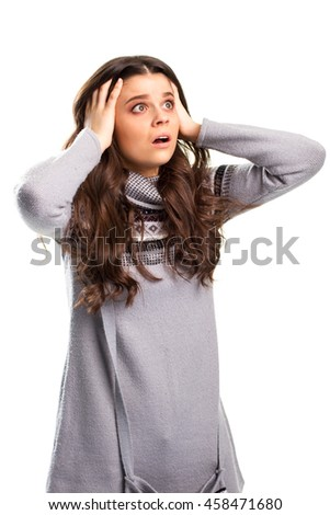 Woman holding head by hands. Young lady with shocked face. Truth is terrifying. You couldn't even imagine. - stock photo