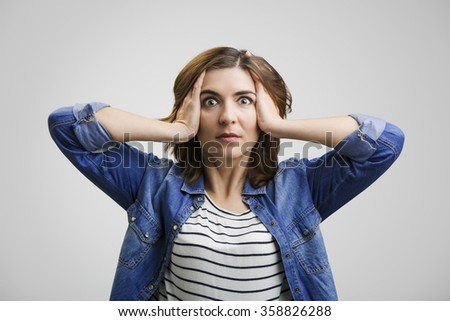 Woman holding head in hands with a astonished expression - stock photo