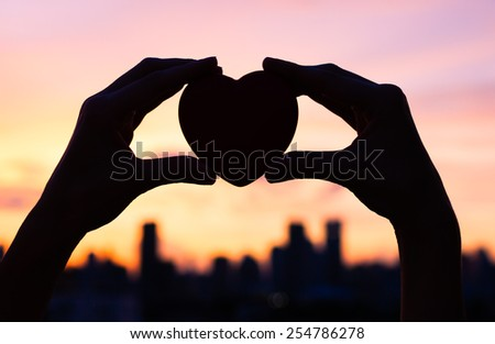 Woman holding heart in the city - stock photo