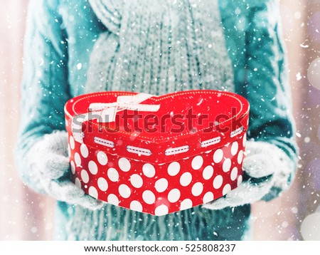Woman holding heart shaped red box with presents close up on light background. Woman hands in teal gloves holding a red heart, Valentine's Day or New Years gift. Winter and Christmas time concept.