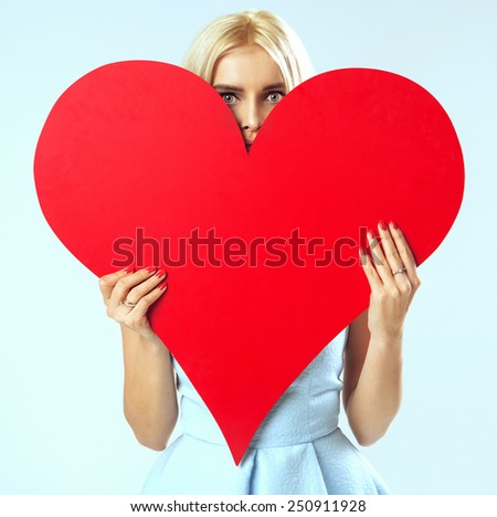 Woman holding heart symbol - stock photo