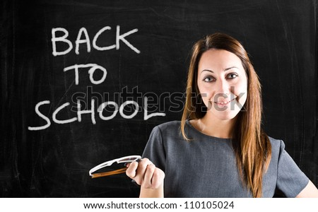 Woman holding her eyeglasses in front of a blackboard - stock photo