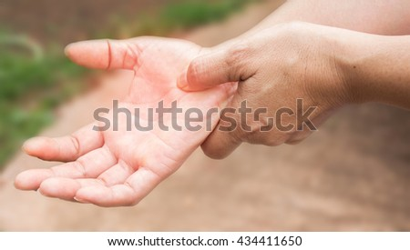 Woman holding her hand. - stock photo