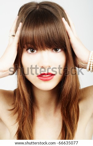 woman holding her head and touching hair - stock photo