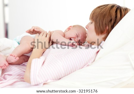 Woman holding her newborn baby in hospital - stock photo