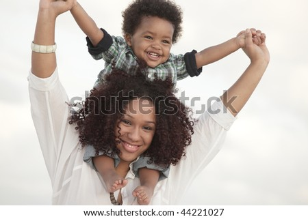 Woman holding her son on her shoulders - stock photo