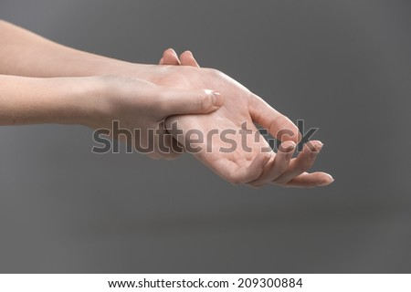 Woman holding her wrist - pain concept. girl feeling wrist Injury on grey background - stock photo