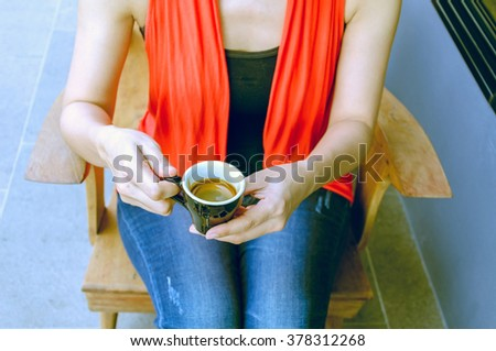 woman holding hot cup of coffee in coffee cafe - stock photo