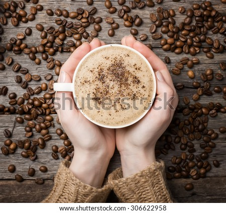 woman holding hot cup of coffee, view from the top - stock photo