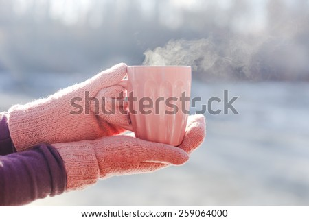 woman holding hot cup of tea - stock photo