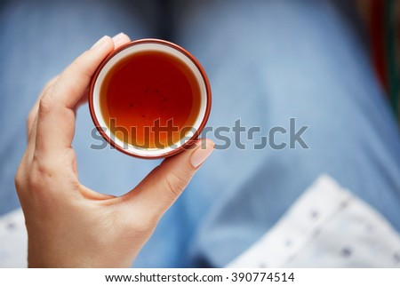 Woman holding hot cup of tea. Female hands holding a mug of hot tea - stock photo
