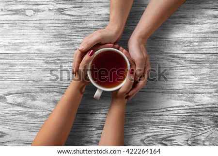 woman holding hot cup of tea with cookies - stock photo