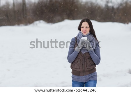 Woman holding hot drink outside