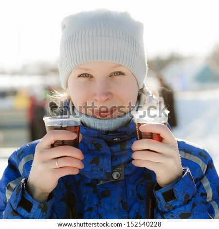 Woman holding hot drink outside in the winter.