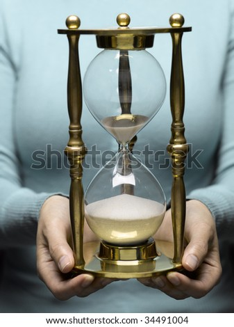 Woman holding hourglass, mid section - stock photo