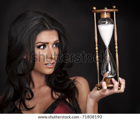 Woman holding hourglass timer - stock photo